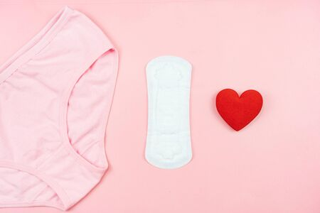 Top view white sanitary napkin,red heart and pink underpants isolated on pink background. Woman hygiene, Concept of critical days, menstruation,health care Archivio Fotografico