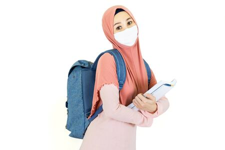 Asian muslim student woman with traditional dress wearing medical face mask,carrying a bag and  books to school Under the outbreak of the virus isolated on white background Banque d'images