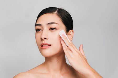 Young beautiful asian woman with clean, fresh and bright skin,holding Cotton swab with positive emotional,isolated on gray background,Beauty Cosmetics and Facial treatment Concept Stock Photo