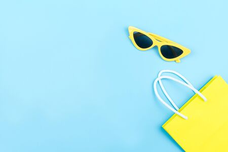Shopping concept,yellow bag and fashion sunglasses isolated on blue background with copy space
