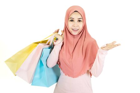 Happy beautiful young muslim asian woman with traditional dress holding color shopping bag isolated on white background