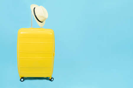 Summer holidays, vacation and travel concept.Yellow Suitcase or luggage bag and sun hat isolated on blue background with copy space