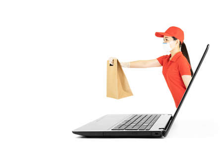 Asian delivery woman in red uniform,Courier in protective mask and medical gloves delivers service under quarantine,Hand giving a paper bag out of laptop screen. Online shopping concept