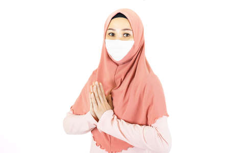 Pray,Greeting,Asian muslim woman with traditional dress wearing medical face mask praying together isolated on white background with copy space, islam muslim greeting eid mubarak
