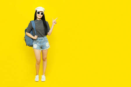 Traveler tourist beautiful young asian woman in casual clothes and sunglasses with Backpack Selfie isolated on yellow background.Summer holidays, vacation and travel concept