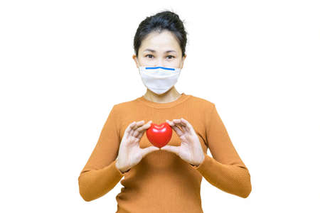 Young asian woman in brown shirt wore medical face mask isolated on white background with red heart,health care concept. Banco de Imagens