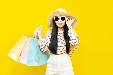 Beautiful excited happy young shopaholic asian woman wearing sungalsses and floppy hat posing isolated over yellow background holding pastel shopping bags and credit card,summer sale concept