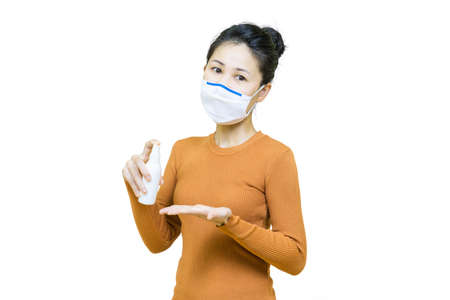 Young asian woman in brown shirt wore medical face mask isolated on white background with Alcohol spray bottle ,health care concept.