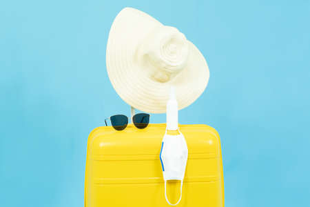 Summer holidays,vacation and travel concept.Yellow Suitcase or luggage bag,sun hat,sunglasses,medical face mask and alcohol Spray,the reopening of the Tourism after the quarantine on blue background