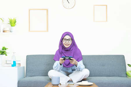 Leisure concept,happy smiling young asian muslim woman in traditional dress wearing glasses with gamepad playing video games on console having fun, resting on weekends at home under quarantine
