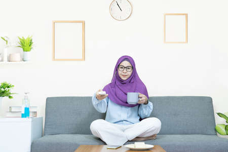 People and leisure concept,Young beautiful asian muslim woman in traditional dress wearing glasses sitting and watching TV,eating snacks and drinking tea,relax at home under quarantine