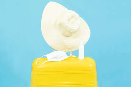 Summer holidays,vacation and travel concept.Yellow Suitcase or luggage bag,sun hat,medical face mask and alcohol Spray,the reopening of the Tourism after the quarantine on blue background