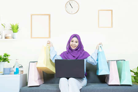 Online shopping concept,Young asian muslim woman in traditional dress wearing glasses with laptop making online shopping and many shopping bag,e-commerce order from home