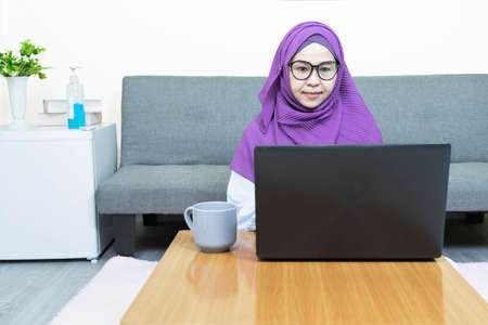 Young beautiful asian muslim woman in traditional dress wearing glasses  using laptop in living room at home,female chatting in social network, shopping or working online, looking at computer screen