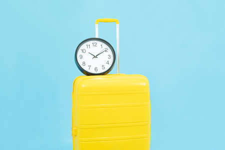 Check in in time before travel, season travel, Summer holidays,vacation duration concept.Yellow Suitcase or luggage bag and clock isolated on blue background