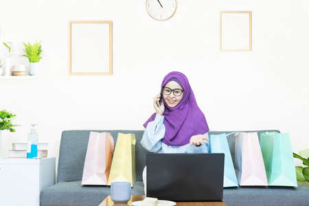 Online shopping concept,Young asian muslim woman in traditional dress wearing glasses with laptop making online shopping and many shopping bag,talking on a phone,e-commerce order from home