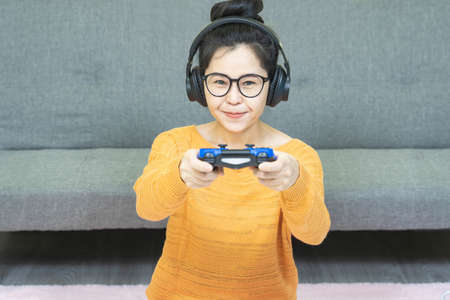 people and leisure concept -close up  happy smiling asian young woman with gamepad playing video games on console having fun, resting on weekends at home under quarantine