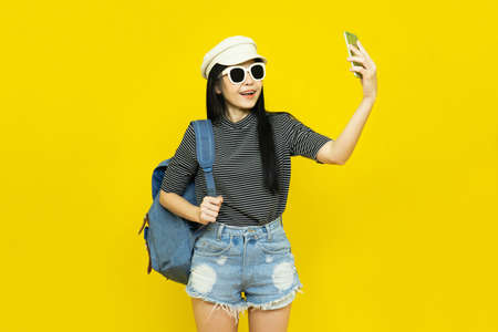 Traveler tourist young beautiful asian woman in casual clothes and sunglasses with Backpack Selfie isolated on yellow background.Summer holidays, vacation and travel concept