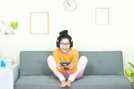 people and leisure concept - happy smiling asian young woman with gamepad playing video games on console having fun, resting on weekends at home under quarantine Banco de Imagens