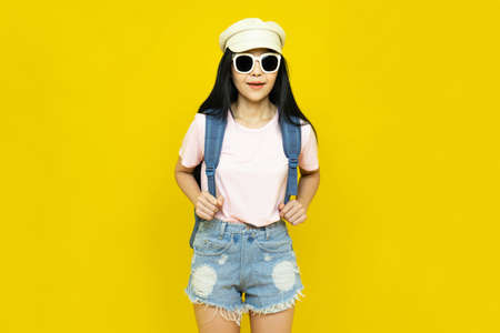 Traveler tourist beautiful young asian woman in casual clothes,cap and sunglasses with backpack isolated on yellow background.Summer holidays, vacation and travel concept