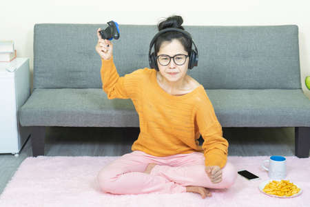 people and leisure concept -Angry asian young woman with gamepad playing video games on console and lose, resting on weekends with snack at home under quarantine