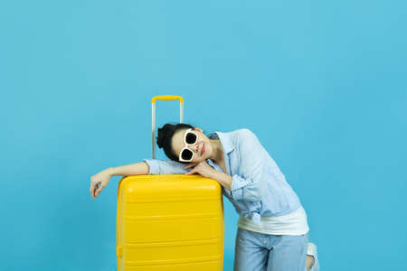 Summer holidays, vacation and travel concept.Happy traveler tourist beautiful young asian woman in casual clothes and sunglasses with yellow suitcase or luggage bag isolated on blue background