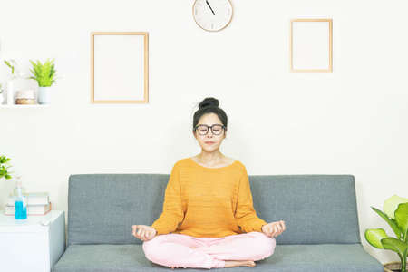 people and leisure concept -Young asian woman meditate on the sofa resting on weekend at home under quarantine Banco de Imagens