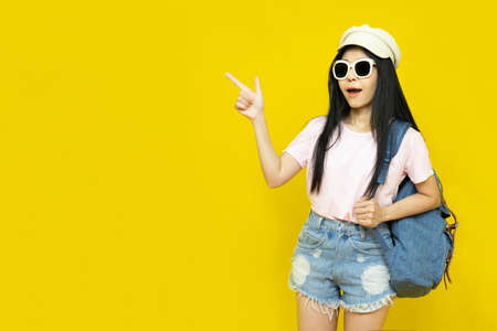 Traveler tourist beautiful young asian woman in casual clothes, cap and sunglasses with backpack isolated on yellow background.Summer holidays, vacation and travel concept Banco de Imagens