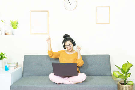people and leisure concept - happy smiling asian young woman with laptop having fun, resting on weekends at home under quarantine