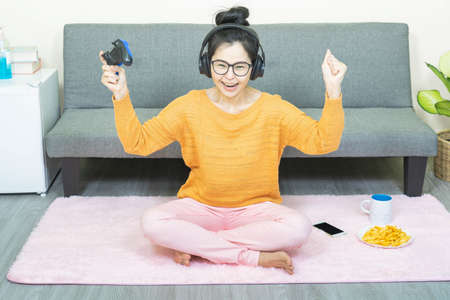 people and leisure concept -young beautiful asian woman wore glasses, sitting on gray sofa in living room ,work online lifestyle,relax at home with coffee under quarantine