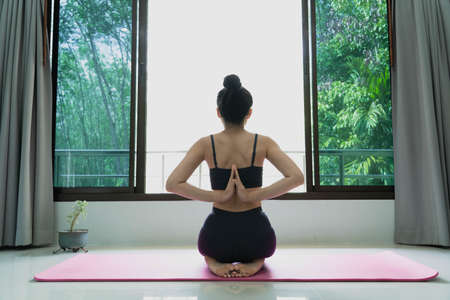 fitness, people and healthy lifestyle concept -woman wearing sportswear practicing yoga with namaste behind the back, sitting in seiza exercise, vajrasana pose, working out at home,rear view Banco de Imagens