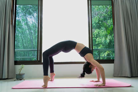 fitness, people and healthy lifestyle concept -Young beautiful asian sports woman performs the exercises stretching in room at home doing bridge pose.Low angle side view