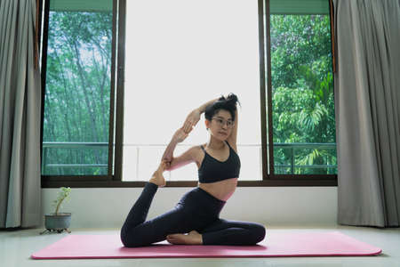 fitness, people and healthy lifestyle concept - Woman wearing sportswear practicing mermaid asana at home for health and a firmer body.Eka pada rajakapotasana pose