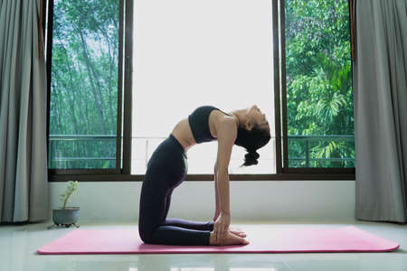 fitness, people and healthy lifestyle concept -Young attractive asian woman practicing yoga stretching in Ustrasana exercise Camel pose working out warm up muscles
