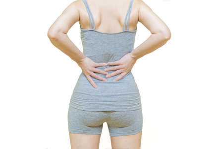 behind body of a woman in gray clothes put her hands on the back area at spot of ache or waist pain, Health-care concept on white background