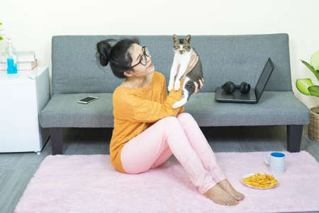 selective focus young beautiful asian woman wore orange knitwear,sitting in living room,playing with a cat,relax at home under quarantine