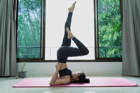 fitness, people and healthy lifestyle concept - Young beautiful asian woman in sportswear suit, doing yoga in shoulderstand at home Banco de Imagens