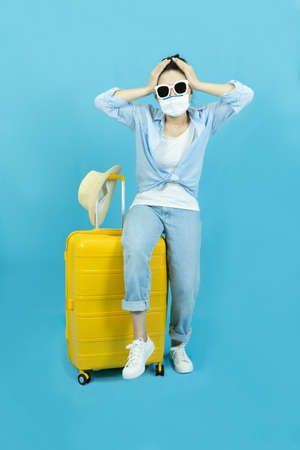 A young woman with a protective medical mask on her face, sitting on a yellow suitcase.The concept of travel, quarantine and coronavirus
