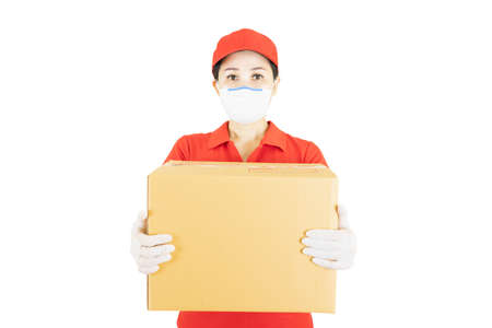 Delivery postal service asian woman in red uniform isolated on white background working as courier or dealer holding and delivering package wearing red cap,medical face mask and gloves with box.