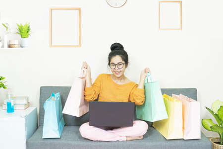 Online shopping concept. Happy young asian woman with laptop making online shopping and many shopping bag ,e-commerce order from home,online payment of financial management