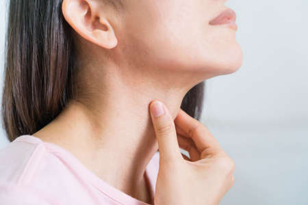 Woman with hands holding her Throat in pain.Health-care Concept.Selective focus