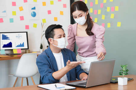 asian small business startup group wearing protective mask for covid19 protection corona flu prevent healty ideas concept office background.The work with new normal lifestyle in office. Banco de Imagens