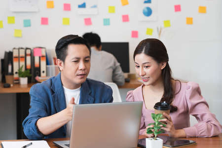 Senior male manager on the job training his colleague in the team for new project and work planning,teach trainee new worker learning new skill at workplace,supervising or teamwork concept