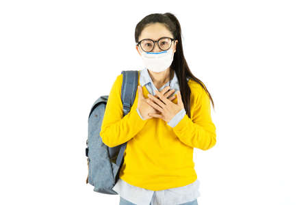 Concept of  virus quarantine. Young Asian woman wearing hygienic mask to prevent infection carry backpack wearing yellow shirt isolated on white background Standard-Bild