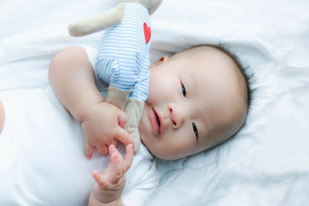 Cute asian newborn toddler with a toy on white bed at home. Standard-Bild