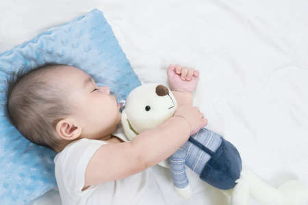 Selective focus portrait of a sleeping Charming baby Cute newborn sleeps with a toy teddy bear on comfortable bed Standard-Bild