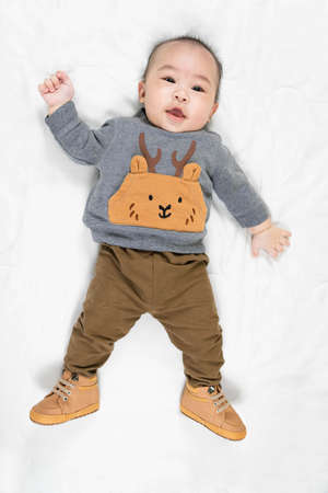 Cute 4 months little asian baby boy in stylish outfit and baby boots lying on soft blanket smiling happily at home, top view Standard-Bild