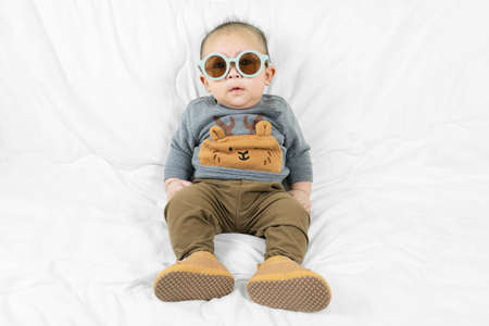 Cute 4 months little asian baby boy in stylish outfit wear glasses and baby boots sitting on white blanket cool and happily at home,kid fashion. Standard-Bild