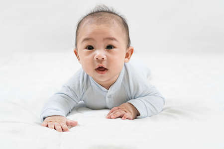 Morning Time.Adorable newborn kid during tummy time smiling happily at home.Portrait of cute smiling happy asian baby boy crawling on bed on the white blanket in bedroom. Standard-Bild