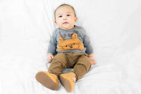 Cute 4 months little asian baby boy in stylish outfit and baby boots sitting on white blanket cool and happily at home,kid fashion.